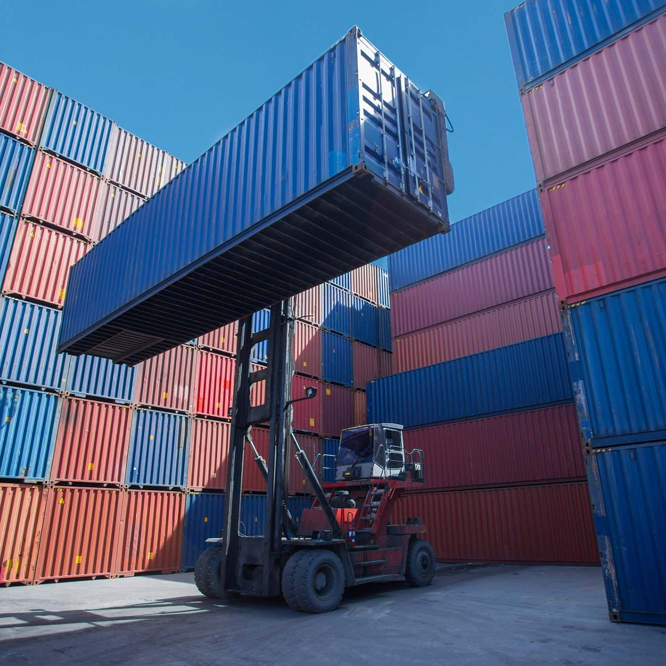 Forklift truck lifting cargo container in shipping yard or dock